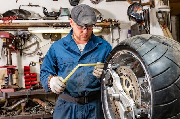 修理キットでオートバイのタイヤを修理する男 Premium写真