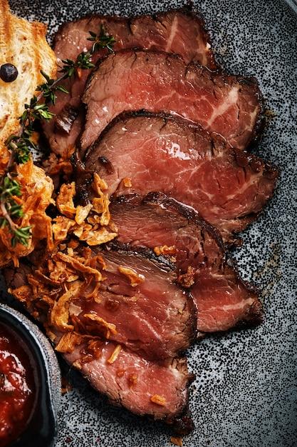 ジューシーなローストビーフとチャバタのトマトソースが美しくスライスされ、皿に並べられます Premium写真