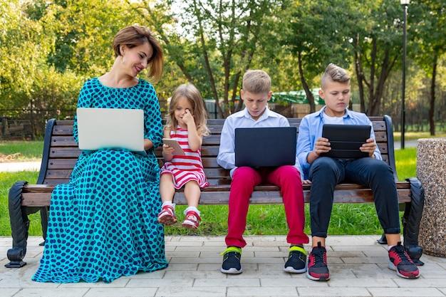 ベンチに座っているガジェットと若い家族 Premium写真