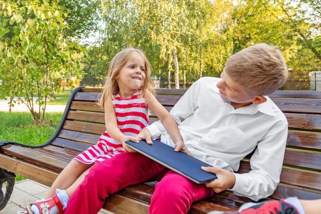 Брат и сестра в парке на скамейке отнимают друг у друга ноутбук Premium Фотографии