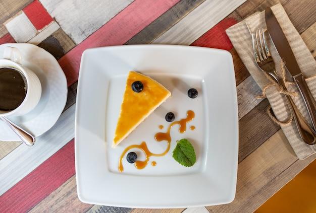 白い皿にブルーベリーソースと木製のテーブルの上のコーヒーカップのチーズケーキ Premium写真