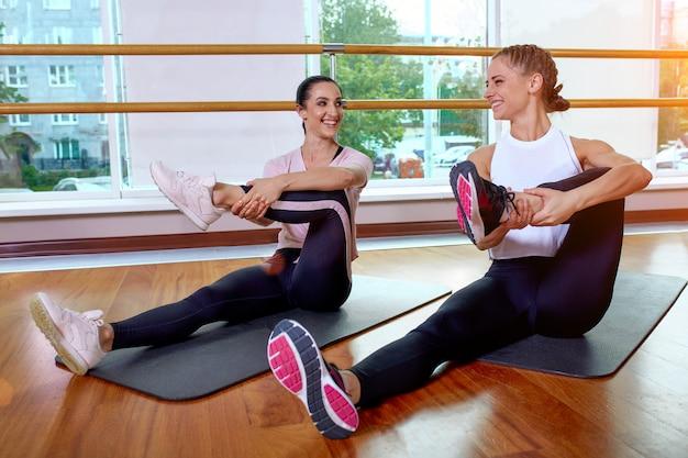 フィットネスグループは、フィットネスレッスンで筋肉を伸ばすためのエクササイズを行います。 Premium写真