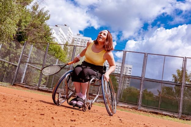 テニスコートでテニスをしている車椅子の若い女性を無効に。 Premium写真