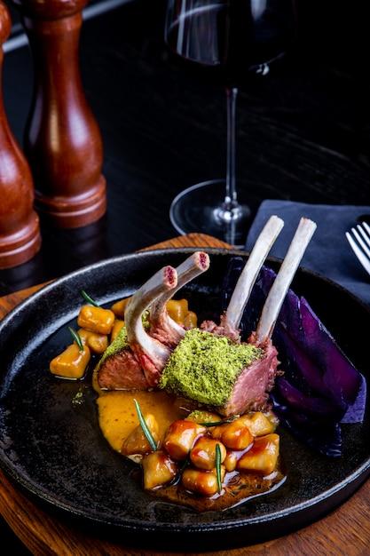 レストランの設定でキャラメル、コショウ、スパイスのソースと野菜とラムチョップのクローズアップ。 Premium写真