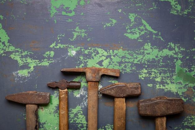 古いハンマーとさびた釘のセット。金属表面のツール。 Premium写真