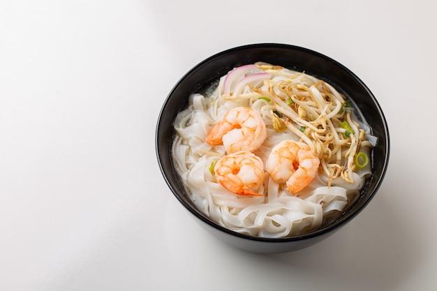 黒のボウルにエビと伝統的なベトナム麺スープフォー Premium写真