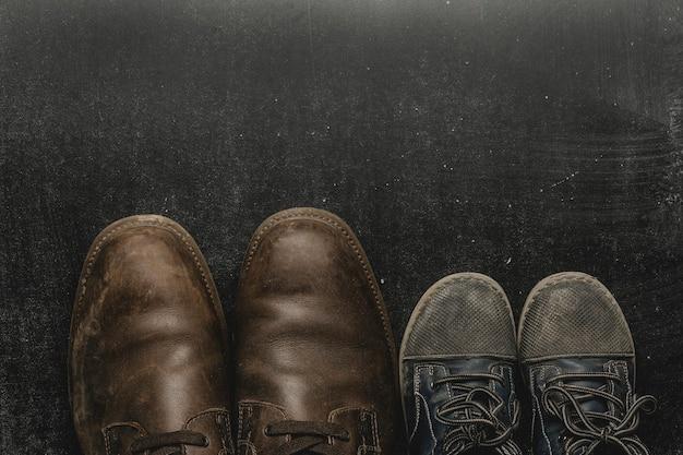 Папа сапоги и детские туфли, концепция отцов день. Premium Фотографии