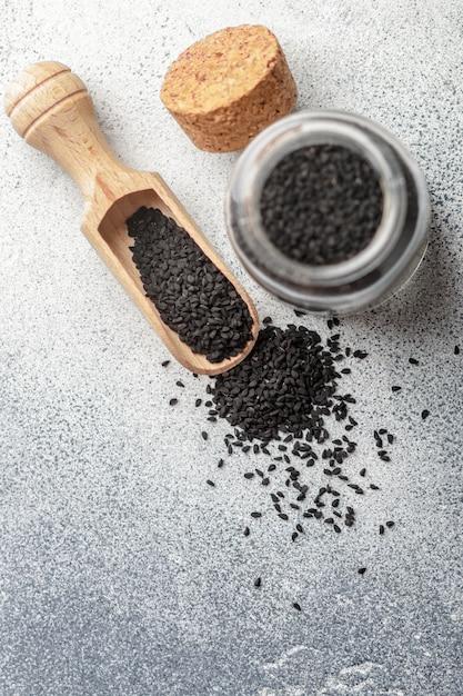 木のスプーンとグレーのガラス瓶に黒のクミンの種子 Premium写真