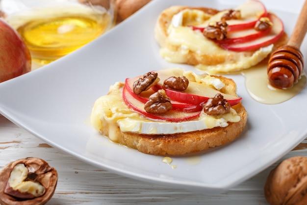 ブリーチーズまたはカマンベールチーズ、リンゴ、クルミ、蜂蜜のブルスケッタサンドイッチ Premium写真