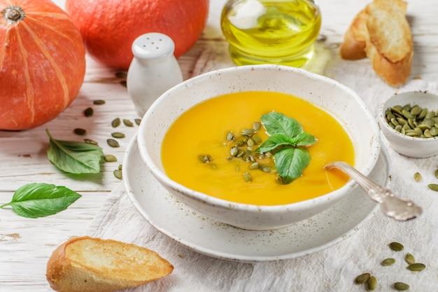 オリーブオイル、種子、バジルを使った食事ベジタリアンカボチャクリームスープのピューレ Premium写真