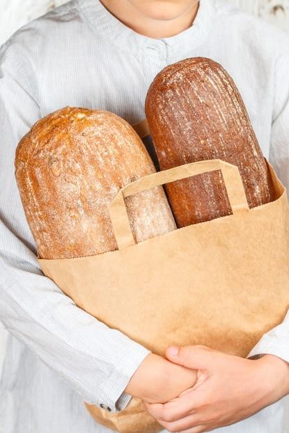 Две буханки хлеба в бумажном пакете в руках Premium Фотографии