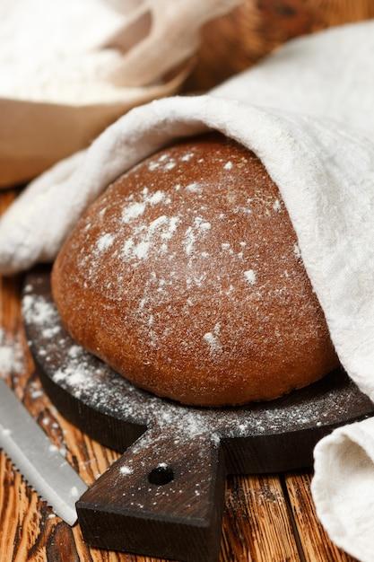 焼きたての自家製パン、小麦粉、古い木製のテーブルにナイフ Premium写真