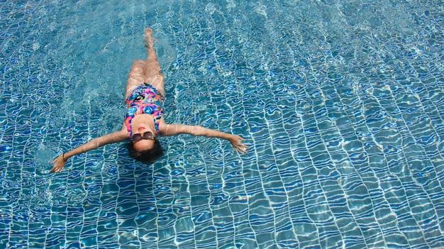 水晶のような水の上に広い腕を開けてプールをリラックスさせて泳ぐ女性のリアビュー。 無料写真