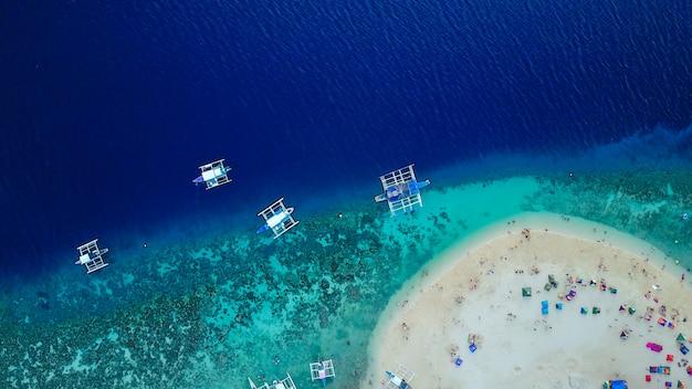 Вид с воздуха на песчаный пляж с туристами, плавающими в красивой чистой морской воде пляжа сумилонского острова, приземляющегося возле ослоба, себу, филиппины. - увеличьте цвет обработки. Бесплатные Фотографии