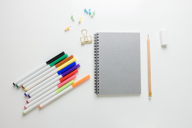 最小限の作業スペース - スケッチブックとコピースペースの上に木製の鉛筆とワークスペースデスクのクリエイティブフラットレイ写真白い背景。トップビュー、フラットレイ写真。 無料写真
