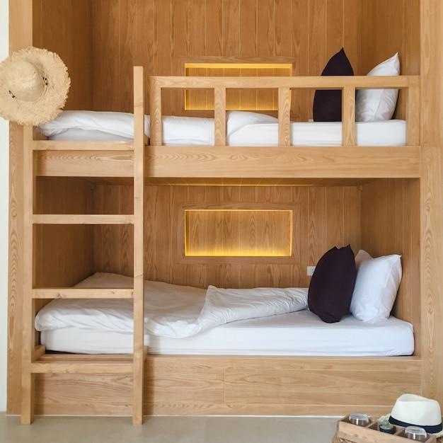 木製の二段ベッドで清潔なホステルルーム。 Premium写真