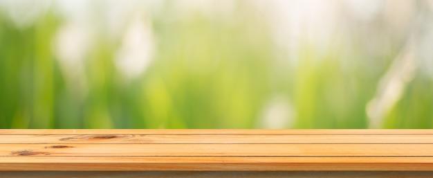 木製のボードの空の表の背景をぼかした。ぼかし木の森の背景の上に展望茶色の木製のテーブル - あなたの製品を表示またはモンタージュのためにモックアップすることができます。春の季節。パノラマバナー Premium写真