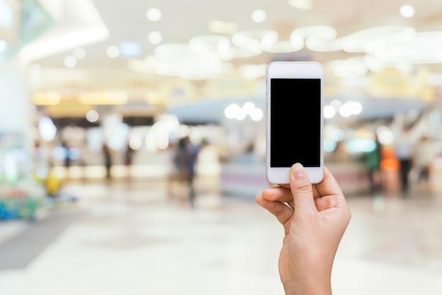ショッピングモールの背景にぼやけた白い画面のスマートフォン、オンラインショッピングのコンセプト、スマートフォンでのショッピング 無料写真