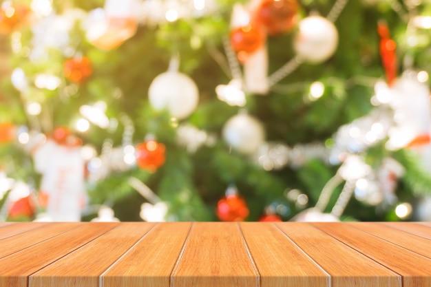 木製のボード空のテーブルの上にぼやけた背景。見通しの茶色の木製のテーブルは、モザイク製品の表示やデザインのレイアウトのためにモックアップすることができますぼかしクリスマスツリーや暖炉の背景に 無料写真