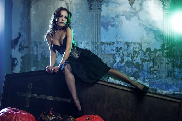Молодая и сексуальная женщина, образ ведьмы на кладбище, сидя на крышке гроба. Premium Фотографии