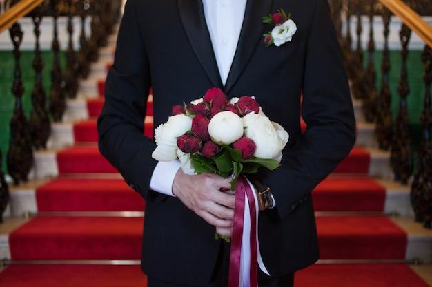 花嫁の花束を持つ新郎は、彼の将来の妻、赤と白の牡丹のクローズアップに会います Premium写真