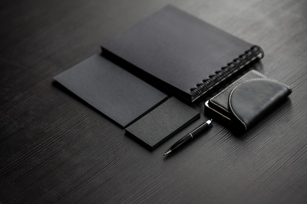 Набор черных макетов на темной женской руке, держащей визитную карточку Premium Фотографии