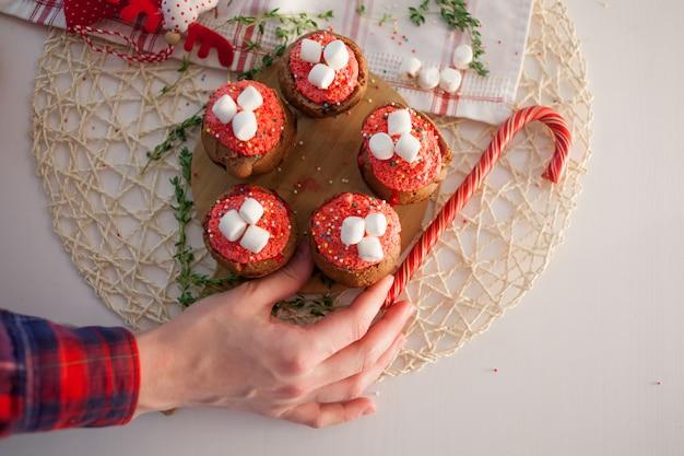 女の子は新年のお祝いのカップケーキ、テーブルの上のチョコレートのマフィンを飾る Premium写真