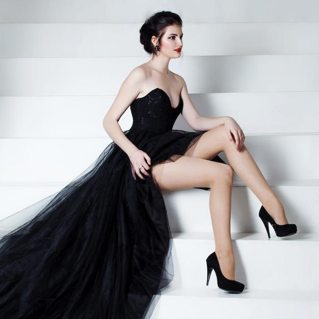 Красота брюнетка модель женщина праздник макияж, сидя на лестнице. Premium Фотографии