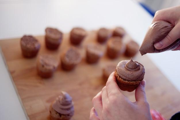 Человек покрывает кекс шоколадным кремом Premium Фотографии