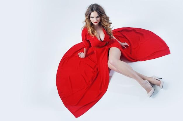 赤いドレスの若い壮大な女性のファッション写真 Premium写真