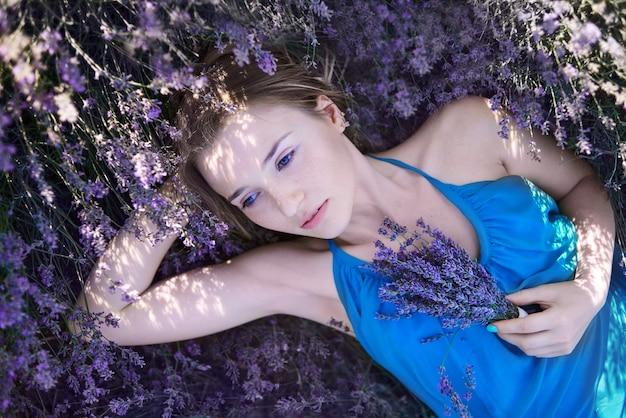 Молодая женщина в романтическое голубое платье отдохнуть в лавандовых полей. романтическая девушка лежит в цветах лаванды и мечтах Premium Фотографии