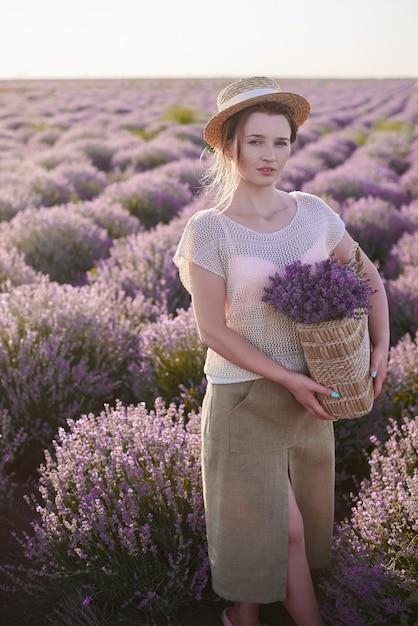 Флорист с плетеной корзиной с лавандой в руках ходить по лугам. женщина ищет лучшие свежие цветы на полях Premium Фотографии