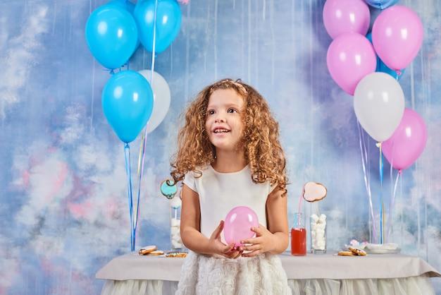 風船で飾られた部屋で子供の面白い誕生日パーティー。幸せな少女は、国際子供の日を祝います。面白い子が家で遊ぶ Premium写真