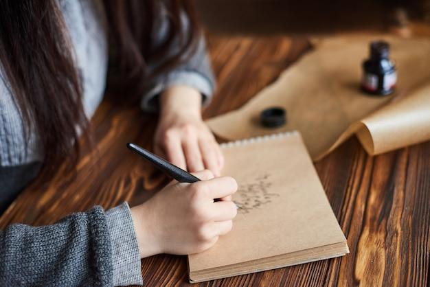 ペーパークラフトのインクペン書道手書きテキストで書く女性 Premium写真