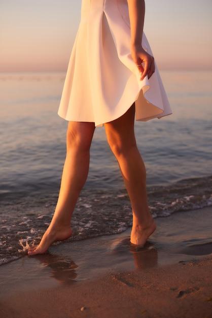 オーシャンリゾートで水に白いドレスを着た素足の女の子。水の上を歩く夏の朝のバイブ Premium写真