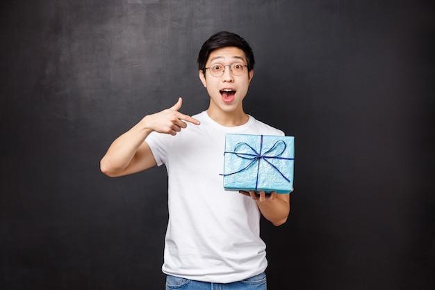 お祝い、休日、ライフスタイルのコンセプト。ギフトボックスの中に何があるかを尋ねる興奮していると好奇心旺盛なかわいいアジアの男の肖像 Premium写真