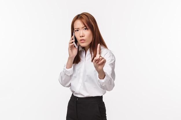 Дай мне одну секунду, момент. занятая серьезная деловая женщина ведет серьезный разговор по телефону, показывает пальцем и просит кого-то подождать, пока она закончит говорить, стоять Premium Фотографии
