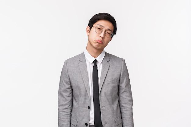 スーツを着た憂鬱でしぶしぶ、感銘を受けていない退屈なアジア人男性の腰までの肖像 Premium写真