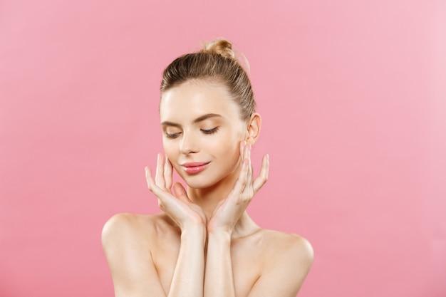 美容の概念 - きれいな新鮮な皮膚を持つ美しい女性は、ピンクのスタジオに閉じます。スキンケアの顔。化粧品。 無料写真