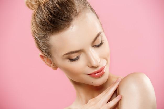 美容の概念 - きれいな肌、自然なメイクアップは、コピースペースと明るいピンクの背景には、美しい白人の女性。 無料写真