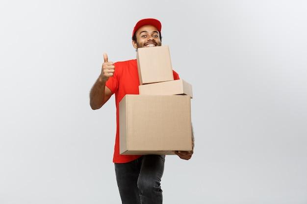Концепция доставки - портрет счастливый афро-американских доставки человек в красной ткани, проведение коробки пакет. изолированные на фоне серой студии. копирование пространства. Бесплатные Фотографии