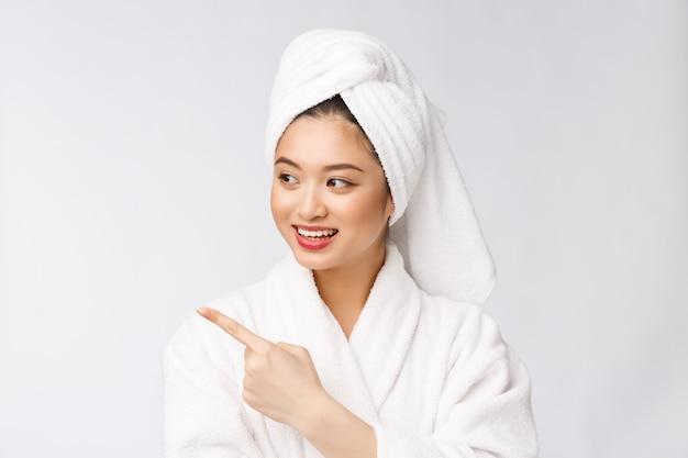 Очаровательная красивая молодая женщина, указывая пальцем. привлекательная красивая девушка получит сюрприз, счастье и любовь к товару, бренду, услуге. Premium Фотографии