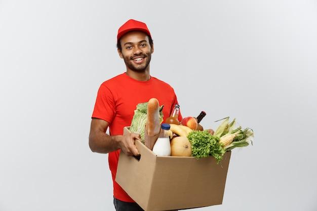 配達のコンセプト - 店から食料品や飲み物のパッケージボックスを運ぶハンサムなアフリカ系アメリカ人の配達人。灰色のスタジオの背景に分離。スペースをコピーします。 無料写真