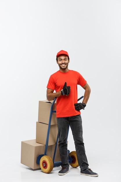 配達の概念 - 肖像画のハンサムなアフリカ系アメリカ人の配達人または宅配便箱のスタックで手のトラックを押す。灰色のスタジオの背景に分離。スペースをコピーします。 無料写真