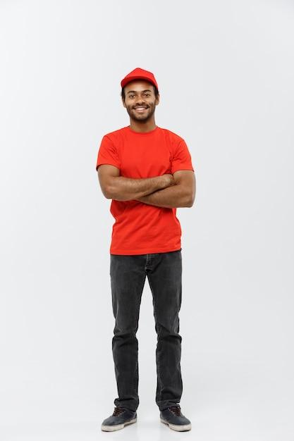 Концепция доставки - красивый афро-американских доставки человек пересек руки над изолированы на фоне серой студии. копирование пространства. Бесплатные Фотографии