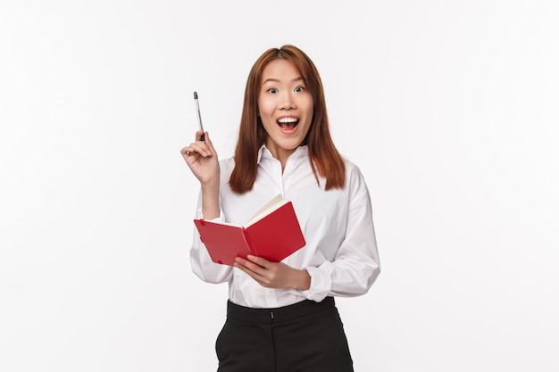 Портрет взволнованной азиатской женщины в белой рубашке, держите красную ручку поднятия тетради в жесте эврика, задыхаясь, удивляясь и улыбаясь, имейте отличную идею, творческий план записывая это, белая стена Premium Фотографии
