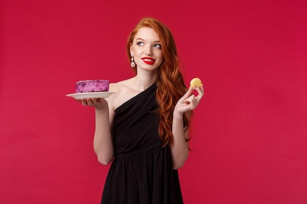 Вдумчивая и мечтательная великолепная стройная рыжая женщина в черном платье думает о еде десерта, заботясь о своем теле, отводит взгляд, обдумывает и улыбается, держит печенье и торт Premium Фотографии