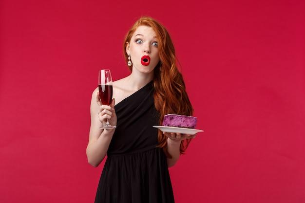 Портрет удивленной и удивленной, потерявшей дар речи милой рыжеволосой женщины в стильном черном платье, держащей бокал с шампанским и торт, удивленно складывая губы, стоят красная стена Premium Фотографии