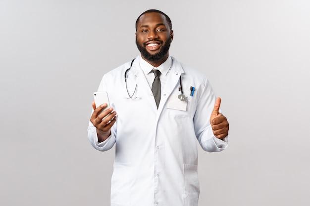 Концепция пандемии и онлайн-медицины. красивый улыбающийся афро-американский врач показывает большой палец вверх, держите смартфон, рекомендует медицинскую помощь врачу или пациенту, обратитесь в службу поддержки или в приложение Premium Фотографии