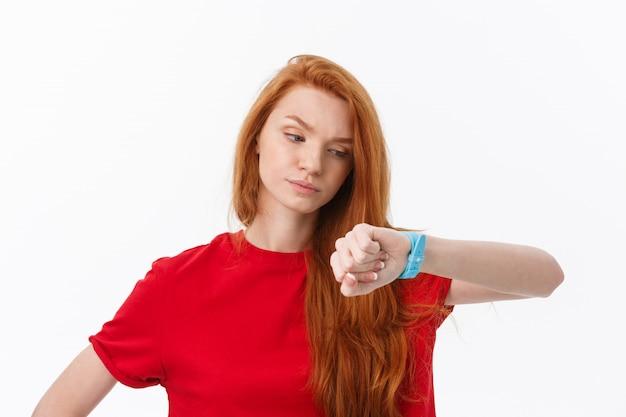 Портрет молодой женщины, указывая пальцем на наручные часы, изолированных на белом Premium Фотографии